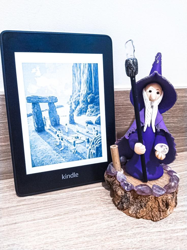 Representação de monumentos de pedras dos celtas, ao lado de um círculo formado por mulheres, em imagem no Kindle, ao lado de um boneco representando Merlin.