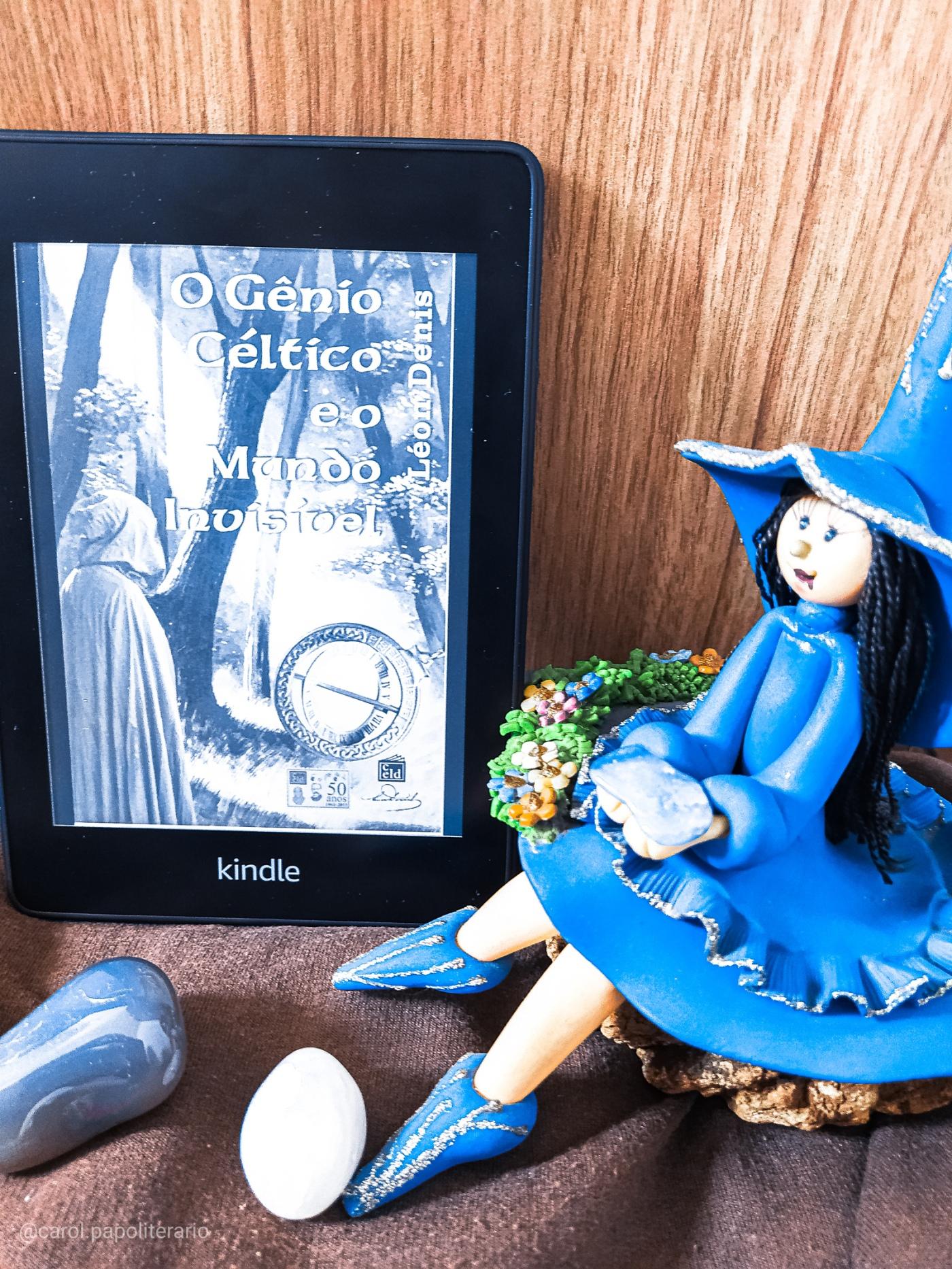 Capa do livro O Gênio Céltico e o Mundo Invisível na versão eBook, no Kindle, ao lado de uma boneca representando Morgana e alguns cristais.