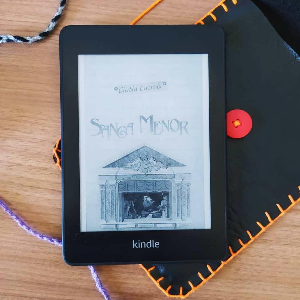 Kindle com a capa do livro Sanga Menor ao centro da imagem. O Kindle está posicionado acima de uma capa artesanal para kindle feita em courino preto, com botão vermelho e costura laranja. Há alguns fios de lã pela imagem, nas cores preta e cinza e roxa.