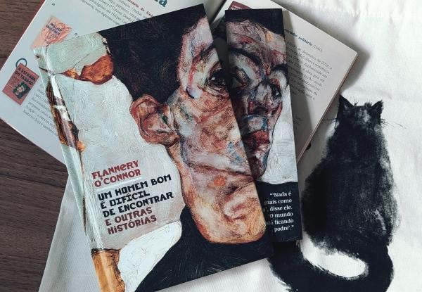 Capa do livro Um Homem Bom é Difícil de Encontrar, com o marcador de páginas personalizado do kit ao lado (à direita). O livro e o marcador estão em cima da revista co conteúdo complementar aberta, que por sua vez, está em cima da ecobag que veio como brinde no kit, mostrando o gato preto em sua estampa.