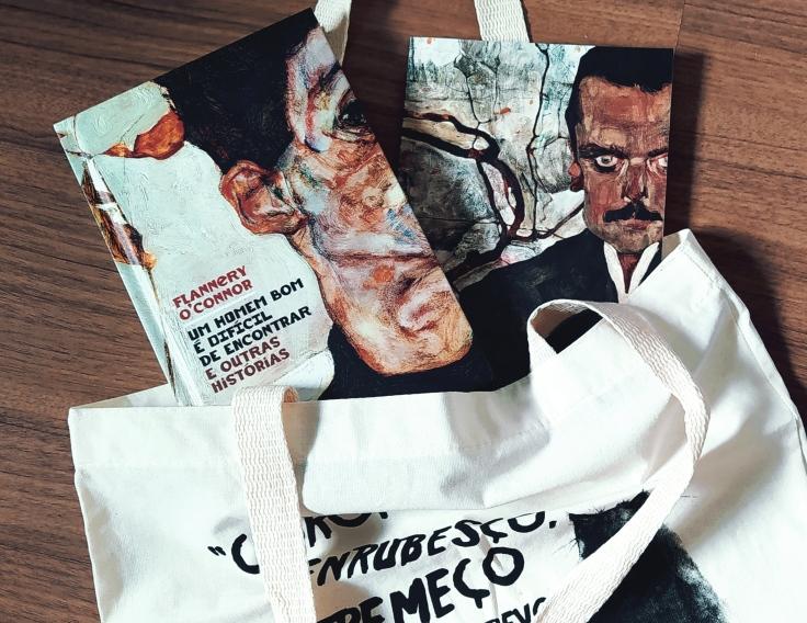 Livro Um Homem Bom é Difícil de Encontrar e outras histórias e revista com conteúdo extra que vem no kit da TAG saindo da ecobag que veio como brinde no kit do mês.
