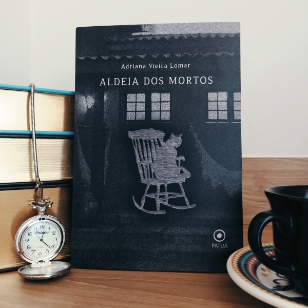Livro Aldeia dos Mortos apoiado em uma pilha de livros, com um relógio de bolso aberto ao lado esquerdo e um pedaço de xícara em apoiada em um pires ao lado direito.