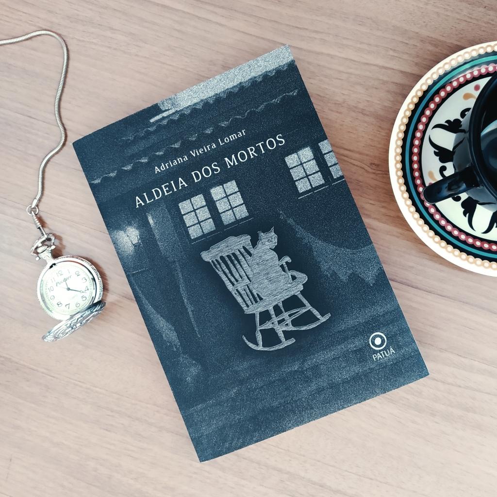 Livro Aldeia dos Mortos ao centro, com um relógio de bolso aberto à esquerda e uma parte de uma xícara acima de um pires à direita.