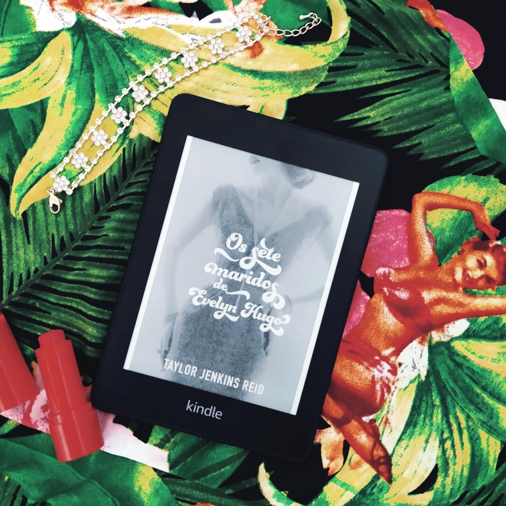 Kindle com a capa de Os Sete Maridos de Evelyn Hugo no centro da imagem. No canto superior esquerdo, há uma pulseira de zircônias. No canto inferior esquerdo, há um batom vermelho aberto. Ao fundo, há um tecido com tema floral e a imagem de uma pin-up.