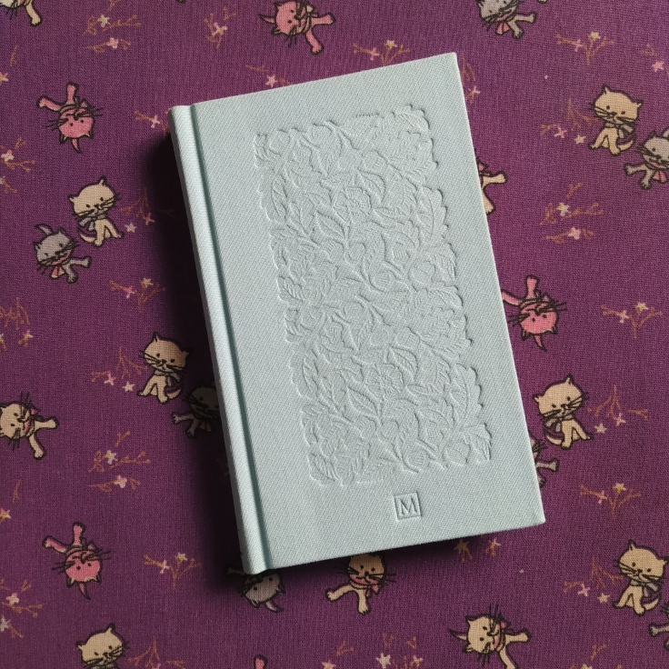 Capa em tecido do livro O Grande Gatsby. Ao fundo, um tecido com tema de gatinhos.