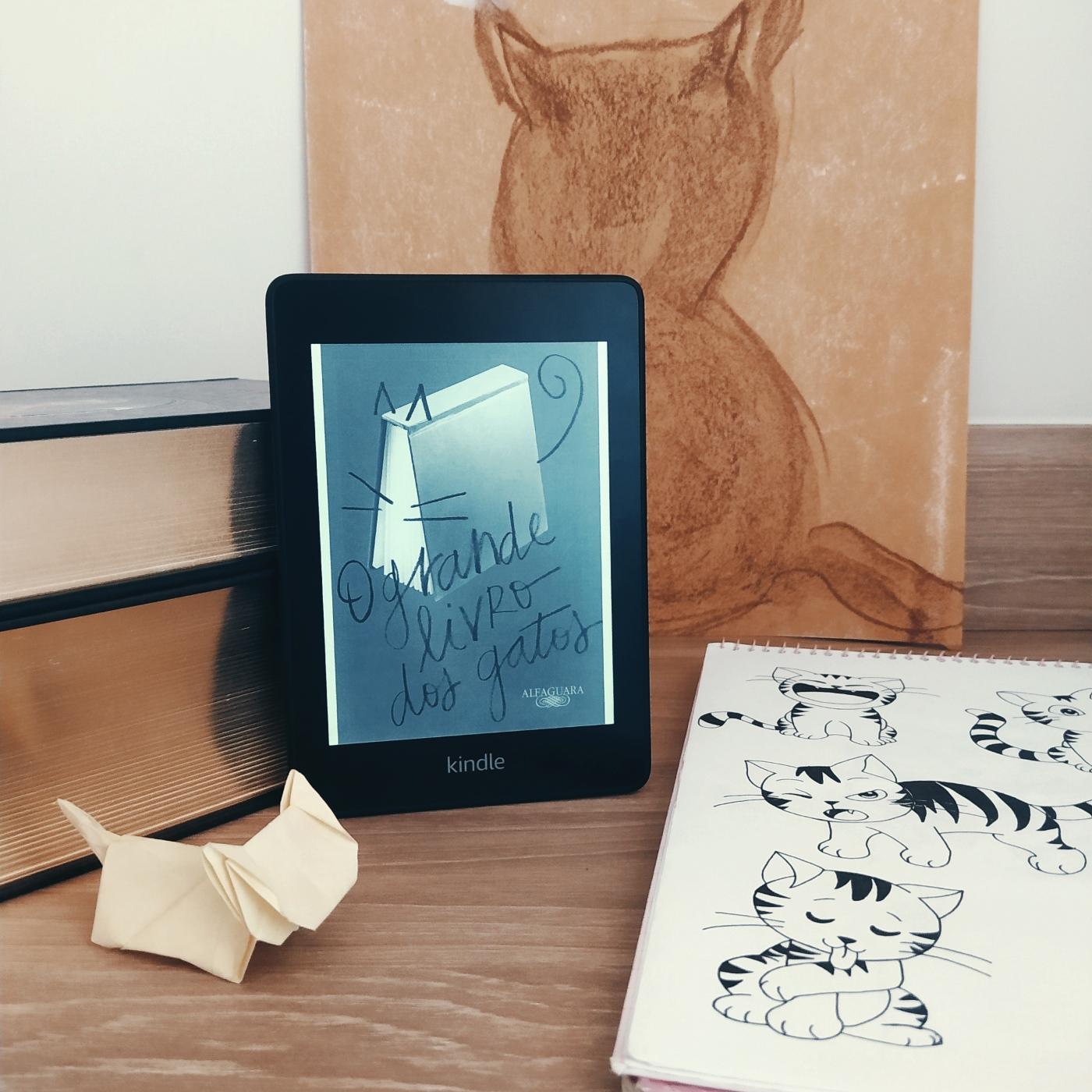 Kindle com a capa de O Grande Livro dos Gatos apoiado em uma pilha de livros, com uma pintura em giz à óleo em papel kraft da silhueta de um gato. À direita, há um caderno com desenhos em nanquim de gatos e à frente há um origami de gato.