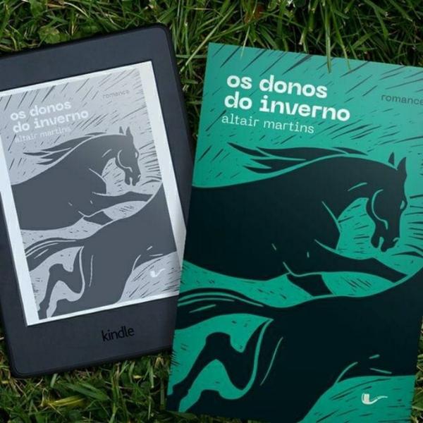Kindle com a capa de Os Donos do Inverno à esquerda da imagem e a capa do exemplar físico do mesmo livro à direita. Ao fundo está um gramado.