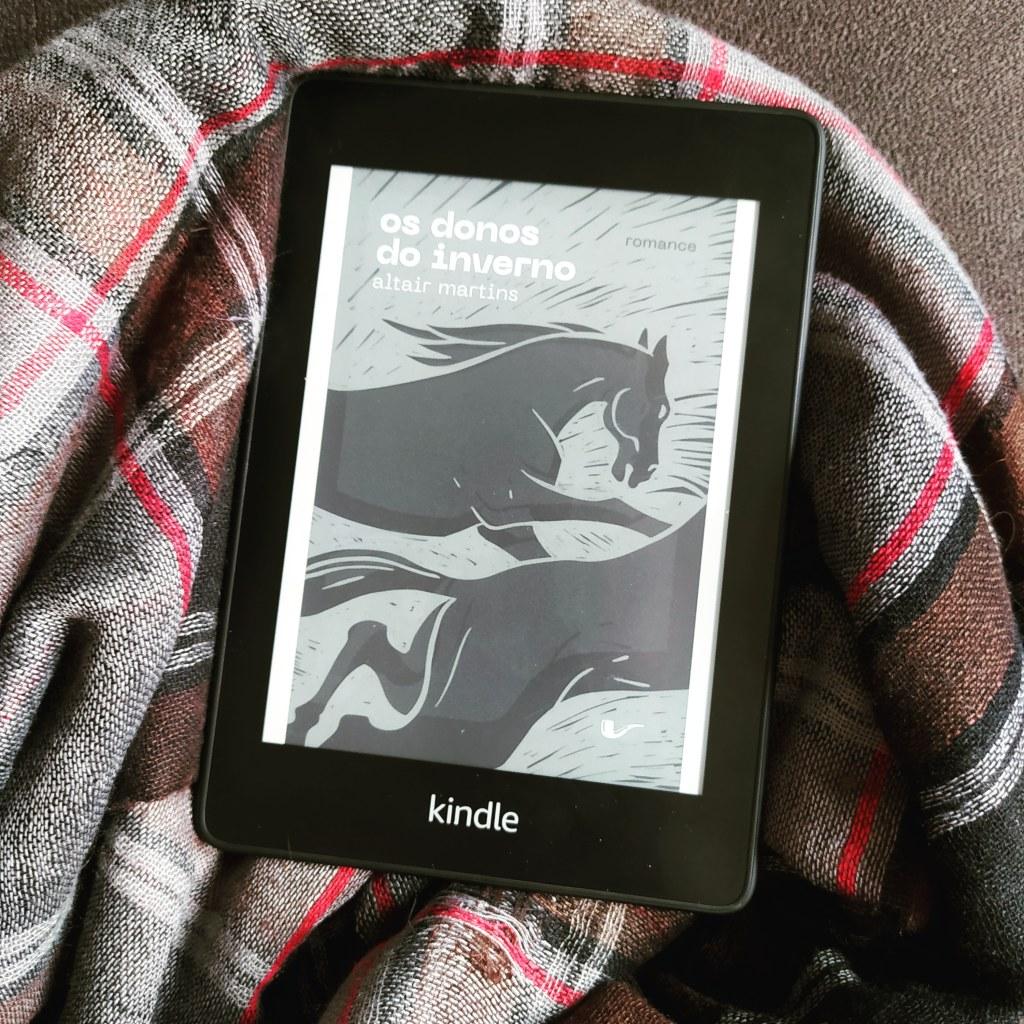 Kindle com a capa de Os Donos do Inverno envolto por uma echarpe xadrez.