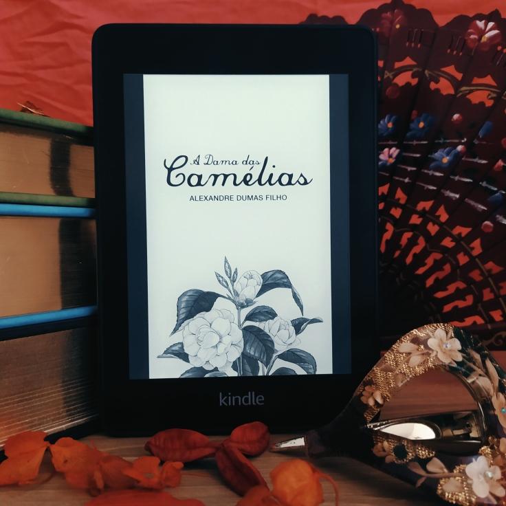 Kindle ao centro da imagem, com a capa de A Dama das Camélias, apoiado em uma pilha de livros. à direita da imagem e ao fundo, há um leque de madeira envernizado e com temas florais aberto. À frente e à direita, há uma presilha de cabelos com tema floral. Há folhas secas espalhadas à frente do Kindle.