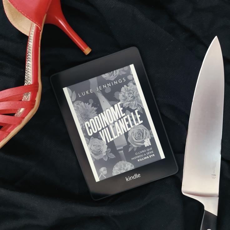 Kindle com a capa do livro Codinome Villanelle, com uma sandália de salto alto vermelha à esquerda e uma faca à direita em um fundo preto.