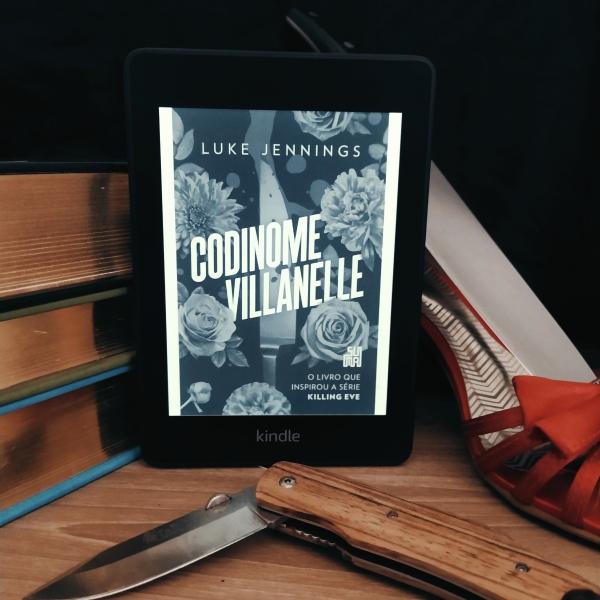 Kindle com a capa do livro Codinome Villanelle apoiado em uma pilha de livros. À direita, há uma sandália de salto alto vermelha com uma faca apoiada dentro dela. Abaixo, há um canivete aberto de forma a fazer um ângulo pouco maior que noventa graus.
