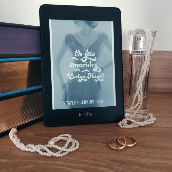 Kindle com a capa de Os Sete Maridos de Evelyn Hugo ao centro da imagem, apoiada em uma pilha de livros. À direita, há um franco de perfume com um colar de pérolas falsas enrolado nele. À frente, há uma pulseira do mesmo material do colar e um par de alianças simples de ouro.