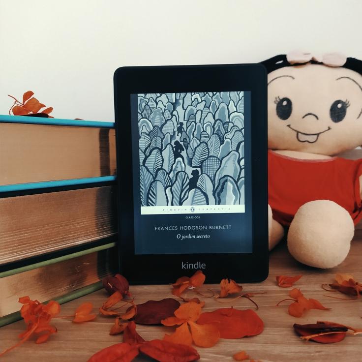 Kindle com a capa de O Jardim Secreto apoiado em uma pilha de livros, com uma boneca de pano da Mônica, personagem de Mauricio de Sousa, à direita, mais ao fundo. Há folhas secas espalhadas em frente ao Kindle.
