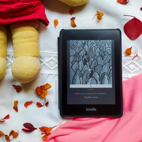 Kindle com a capa do livro O Jardim Secreto, com uma boneca de tecido ao lado, na parte superior esquerda da foto, aparecendo apenas as pernas e um pedaço do tronco e do braço direito. Há pequenas folhas secas espalhadas pela imagem.