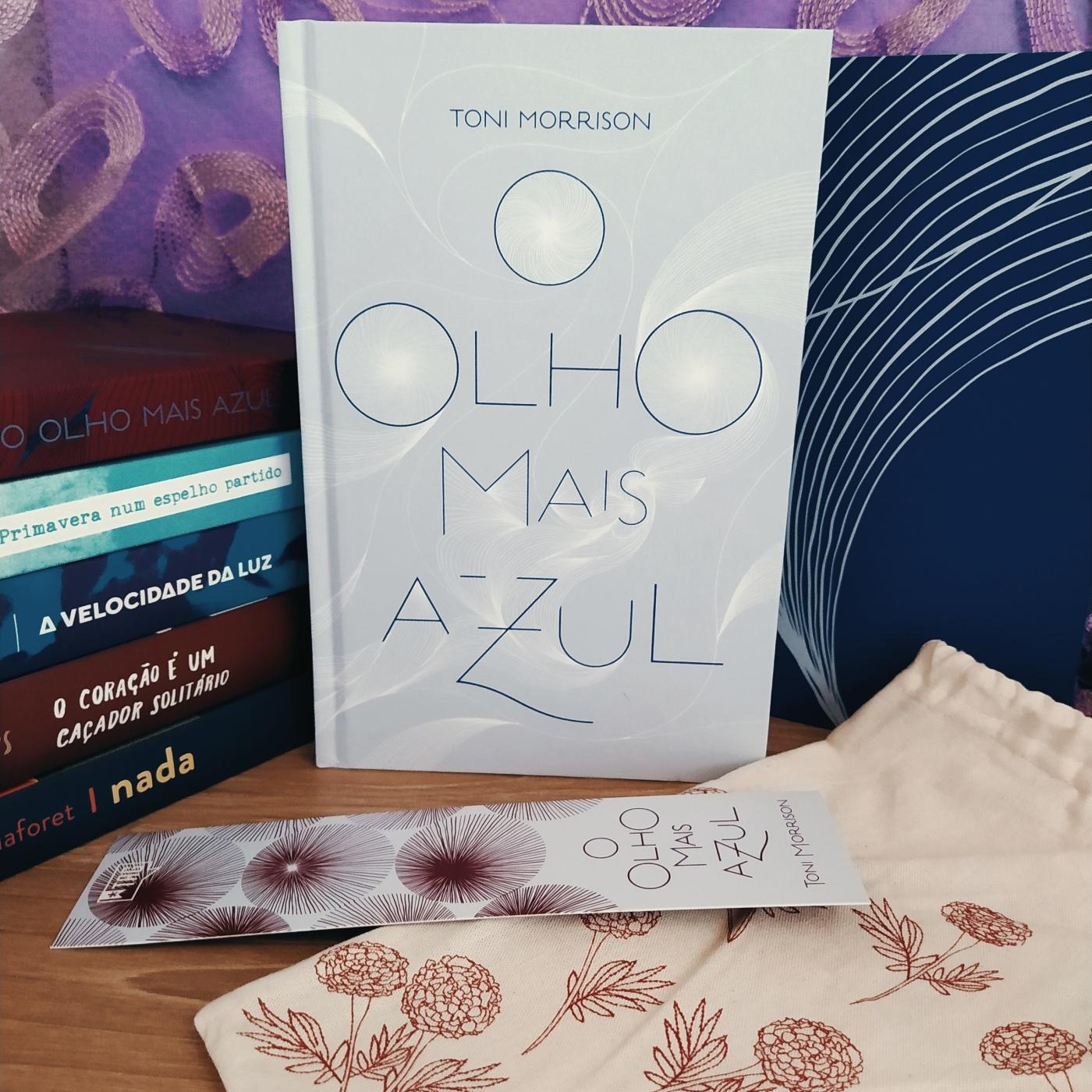 Capa do livro O Olho Mais Azul, com uma pilha de livros anteriores da TAG Curadoria à esquerda e a revista que aocmpanha o kit à direita. Abaixo do livro estão o marcador de páginas personalizado da TAG e o brinde do kit, que é uma pequena ecobag, para carregar um livro. Ao fundo está um tecido roxo.