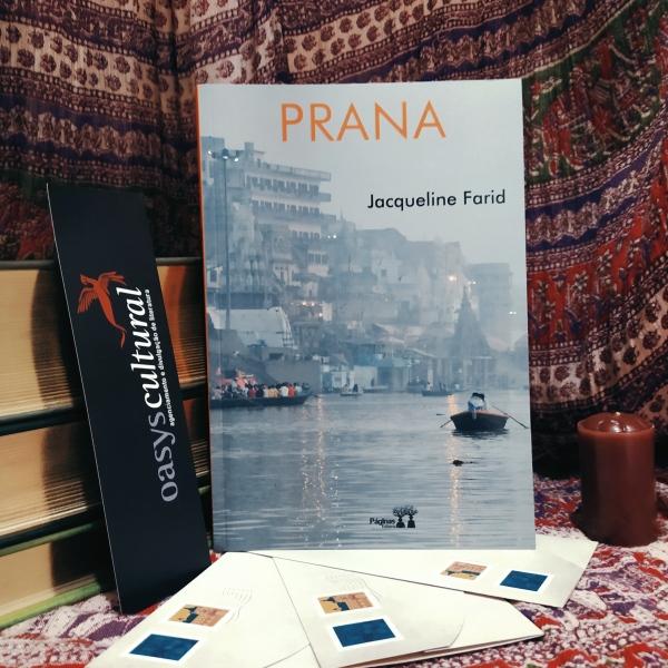 Livro Prana apoiado em uma pilha de livros, com um marcador da Oasys Cultural à esquerda e uma vela à direita. Abaixo, há três envelopes de cartas com selos. Ao fundo, há um tecido com tema que remete à Índia.