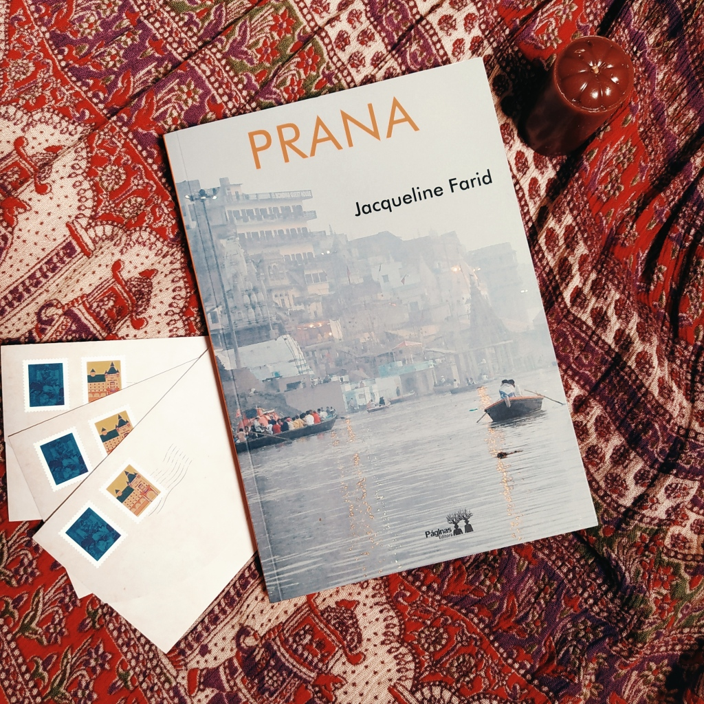 Livro Prana, com uma vela à esquerda e acima e três envelopes de carta à direita e abaixo. Ao fundo, há um tecido com temas que remetem à Índia.