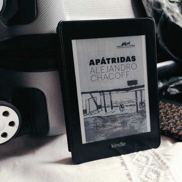 Kindle no centro da imagem com a capa do livro Apátridas, apoiado em uma mala de rodinhas cinza com detalhes em preto, sobre um tecido branco. Ao lado, um livreto com capa de passaporte, com estampa de aviões de papel.