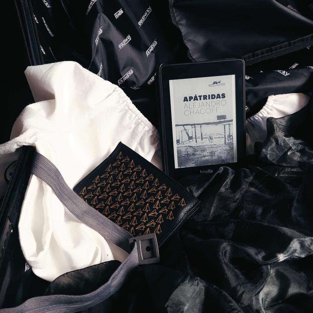 Mala de viagem aberta, com uma camiseta de manga comprida branca aberta com a manga para fora, um tecido preto jogado dentro da mala, um livreto com capa de passaporte com estampa de aviões de papel e um kindle com a capa do livro Apátridas.