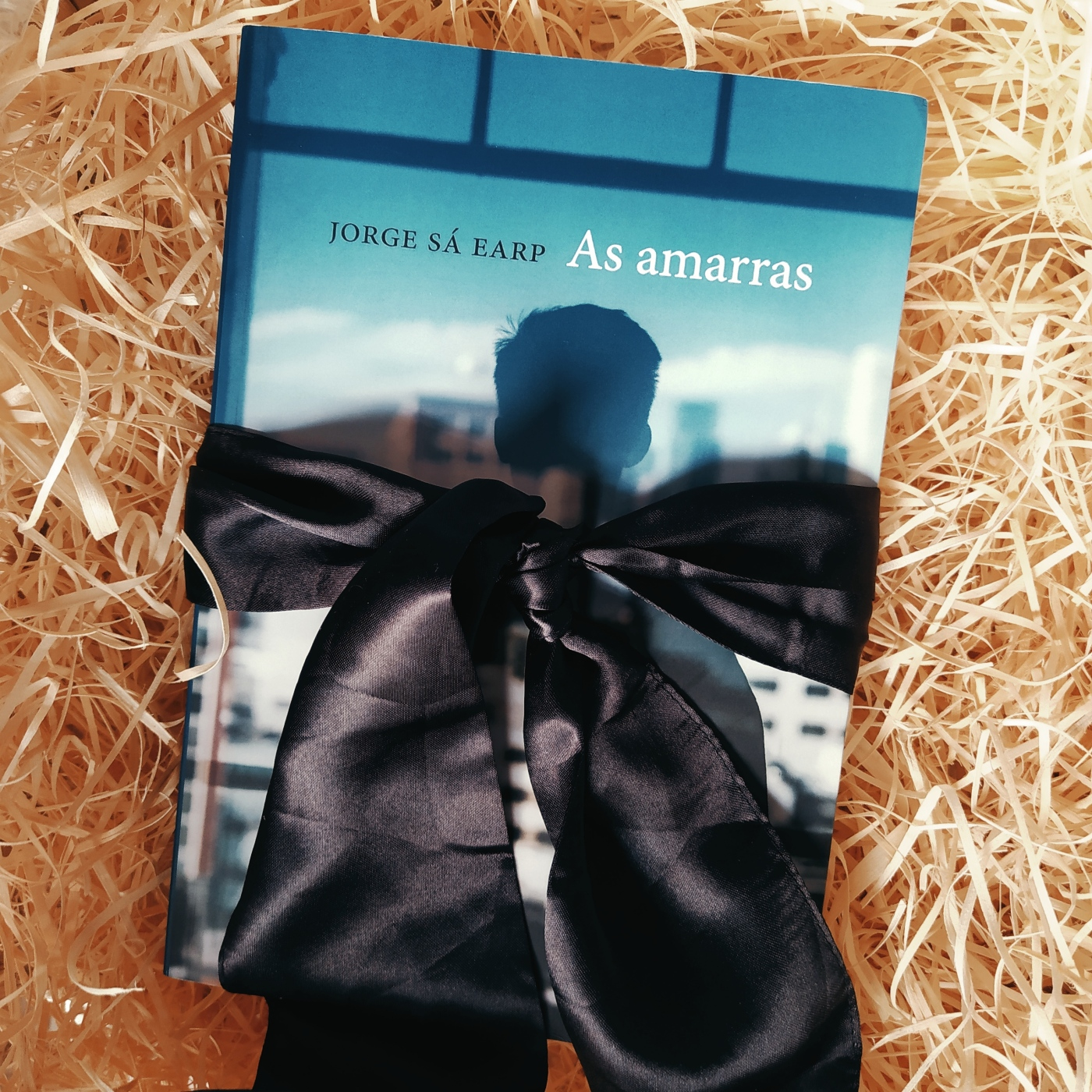 Livro As Amarras no centro da imagem, com uma faixa preta em torno dele fazendo um laço. O fundo é de palha.