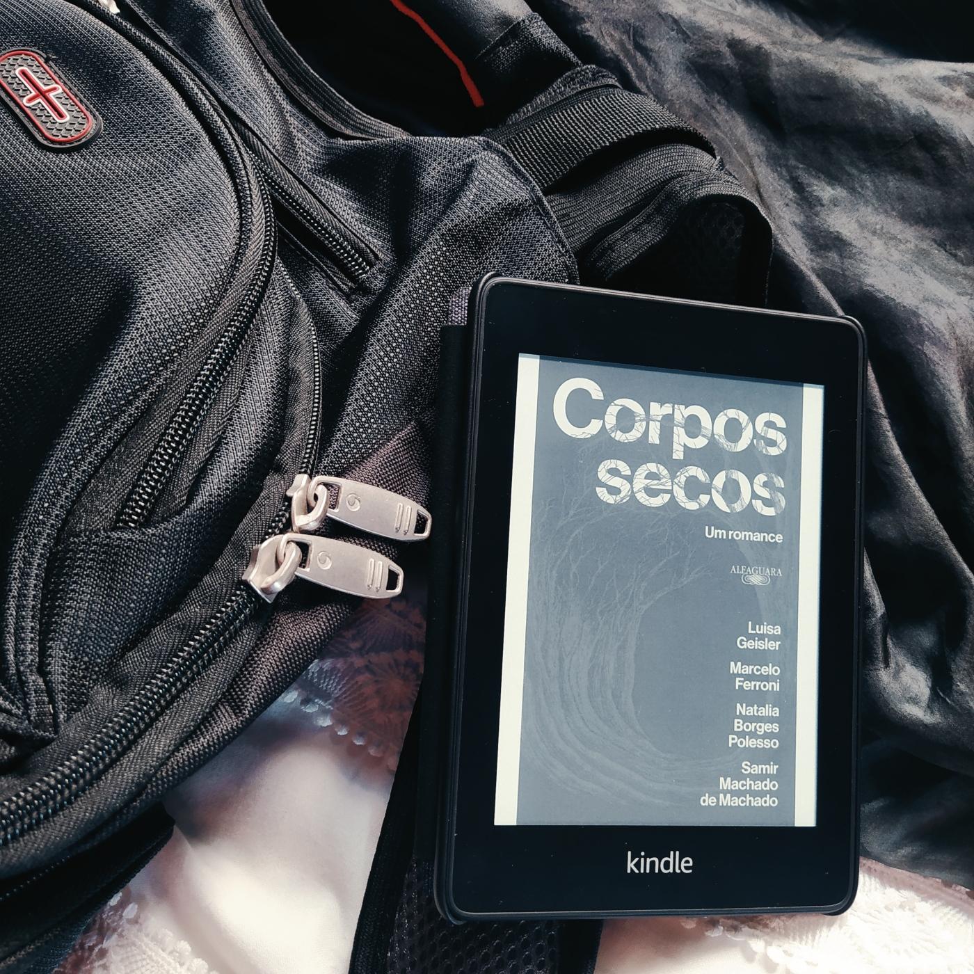 Kindle com a capa do livro Corpos Secos, apoiado em uma mochila preta, que está na metade esquerda da imagem. O fundo é composto de tecidos preto, na parte superior, e branco, na parte inferior.