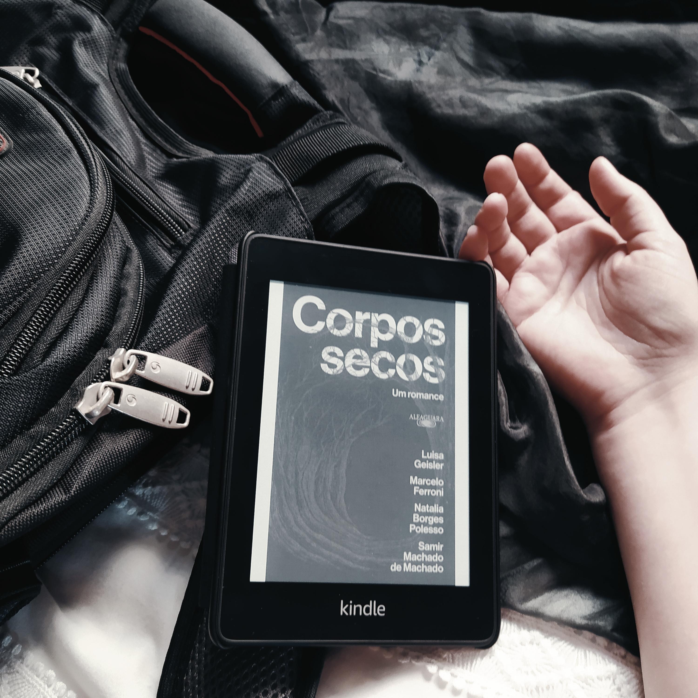 Kindle com a capa do livro Corpos Secos, apoiado em uma mochila preta, que está na lateral esquerda da imagem. Há uma mão caída ao lado do kindle, na parte direita da imagem. O fundo é composto de tecidos preto, na parte superior, e branco, na parte inferior.