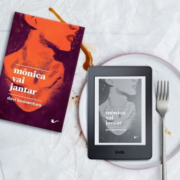 Livro Mônica Vai Jantar na parte esquerda centralizada da imagem. Kindle com a capa do livro Mônica Vai Jantar em cima de um prato, com um garfo ao lado, na parte direita centralizada da imagem. O fundo é branco, com um fio de ketchup passando por baixo do livro físico, me direção ao prato.