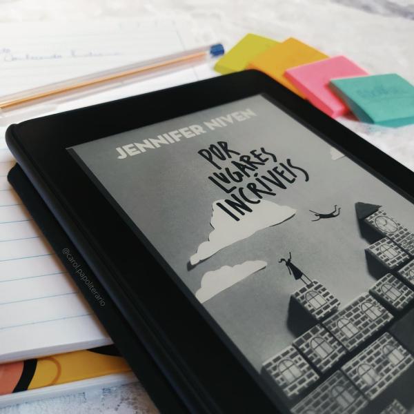Kindle em primeiro plano, com a capa do livro Por Lugares Incríveis. O Kindle está apoiado em um caderno pautado. Há uma caneta bic em cima do caderno, mais ao fundo. Também é possível ver, ao fundo e desfocado, ao lado do caderno, 4 bloquinhos de notas autoadesivas.