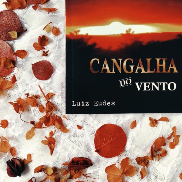 Livro Cangalha do Vento, de Luiz Eudes, na parte superior direita da imagem, com folhas secas em tons de marrom preenchendo o restante da imagem. O fundo é de um tecido branco rendado.
