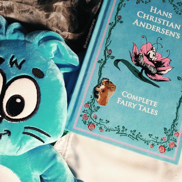 Sansão, o coelho azul da Turma da Mônica, de pelúcia na metade esquerda da imagem. Livro de capa dura azul de contos de fadas de Hans Christian Andersen na metade direita da foto. Há um foto pequena sobre o livro de uma criança em pé, por volta de dois anos de idade. O fundo é composto por tecidos preto, em cima, e branco, embaixo.