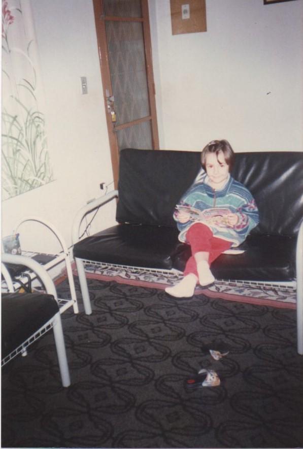 Criança sentada em um sofá, com as pernas cruzadas e com um gibi aberto nas mãos.