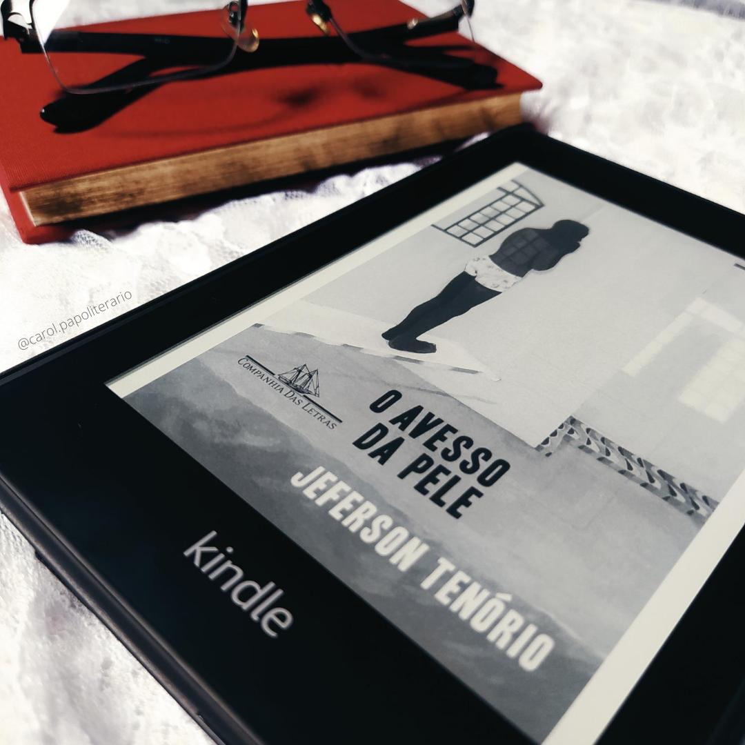 Kindle com a capa do livro O Avesso da Pele em primeiro plano. Ao fundo, está um livro de capa de tecido com um óculos de armação quadrada apoiado em cima.