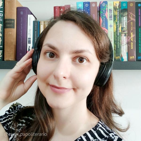 Foto de uma moça sorrindo, com um fone de ouvido estilo headphone, e cabelos soltos. No fundo, há uma estante de livros.
