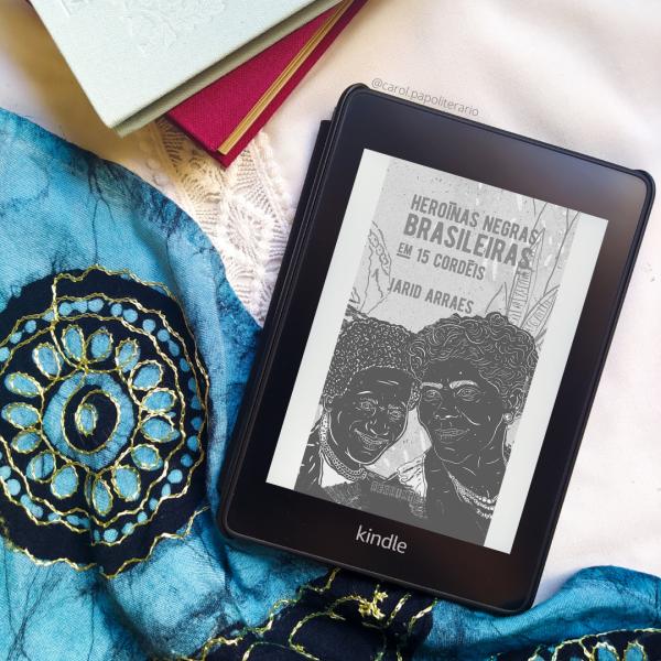 Kindle com a capa do livro Heroínas Negras Brasileiras em 15 cordéis. Há uma pilha de livros com capa de tecido no canto superior esquerdo da imagem. Há um tecido com motivos indianos na metade diagonal inferior esquerda da foto.