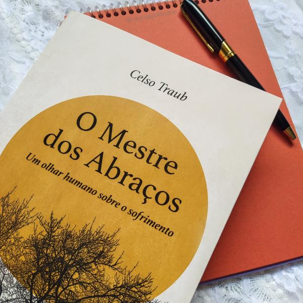 Livro O Mestre dos Abraços em primeiro plano, apoiado em um bloco de anotações sem pauta, com uma caneta elegante em cima do bloco.