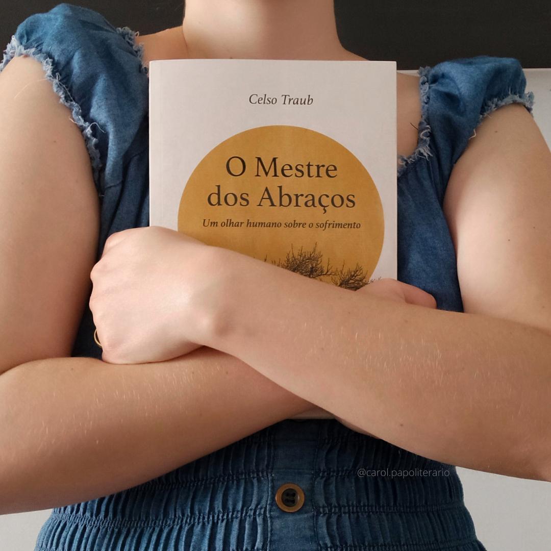 Moça abraçando o livro O Mestre dos Abraços. A cabeça e o corpo da cintura para baixo estão fora da imagem.