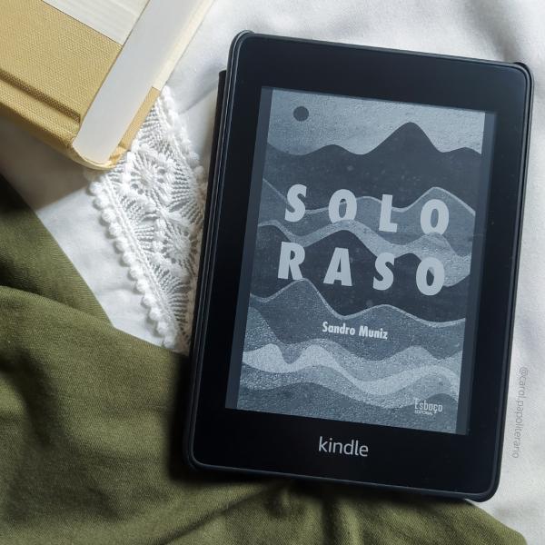 Kindle com a capa do livro Solo Raso, com um tecido no canto inferior esquerdo da imagem e um livro com capa lisa no canto superior esquerdo da imagem.