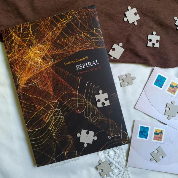 Livro Espiral, com dois envelopes de carta ao lado, no canto inferior direito da imagem, e peças de quebra-cabeça espalhados pela imagem.