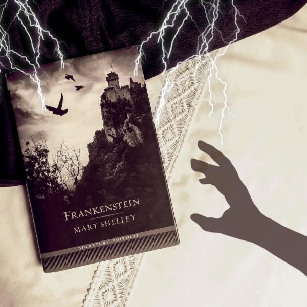 Livro Frankenstein na metade esquerda da foto, com a sombra de uma mão tentando alcançar e pegar o livro, entrando pela direita da foto. Há raios caindo sobre o livro, vindo da parte superior da foto.