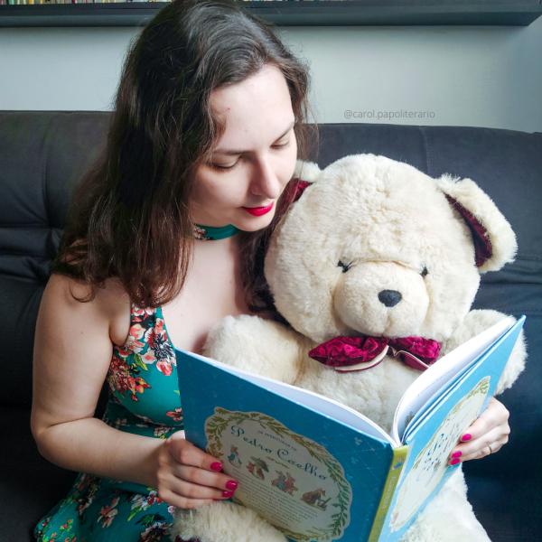 Moça sentada no sofá com um urso de pelúcia no colo. Ela está com um livro infantil aberto, como se estivesse lendo para o urso.