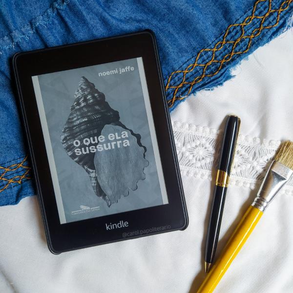 Kindle com a capa do livro O Que Ela Sussura, com uma caneta e um pincel no canto inferior direito da imagem.