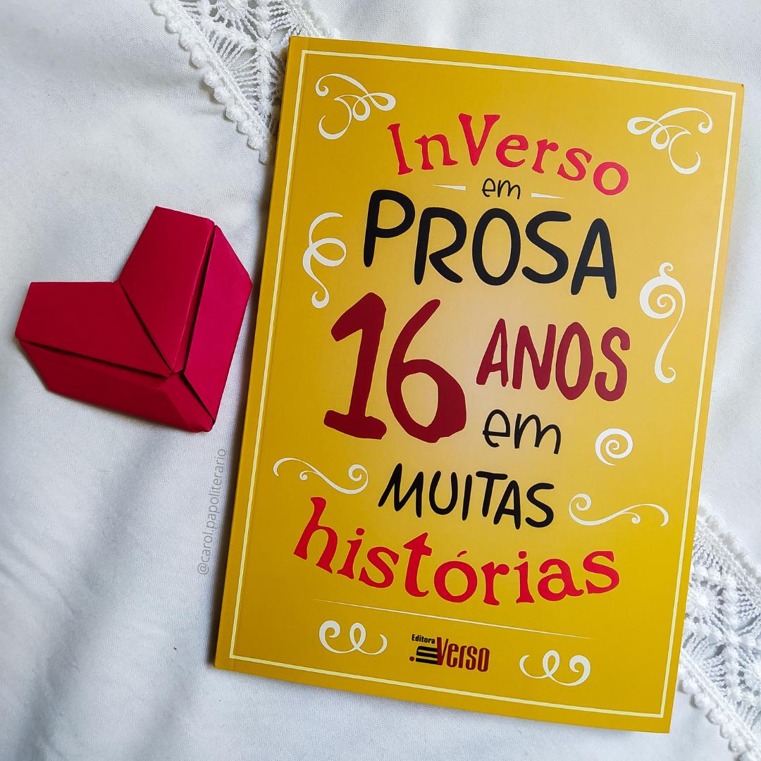 """Livro """"InVerso em Prosa, 16 anos em muitas histórias"""", com um coração de origami ao lado."""