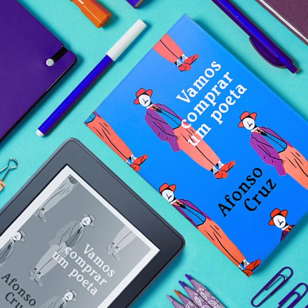 Livro Vamos Comprar um Poeta, ao lado de um Kindle (em 90 graus) com a capa do mesmo livro. Ao redor existem vários objetos de papelaria, como caneta, clips e lápis de cor.
