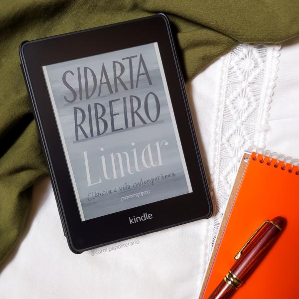 Kindle com a capa do livro Limiar, com um bloco de anotações com uma caneta apoiada em cima à esquerda do Kindle.