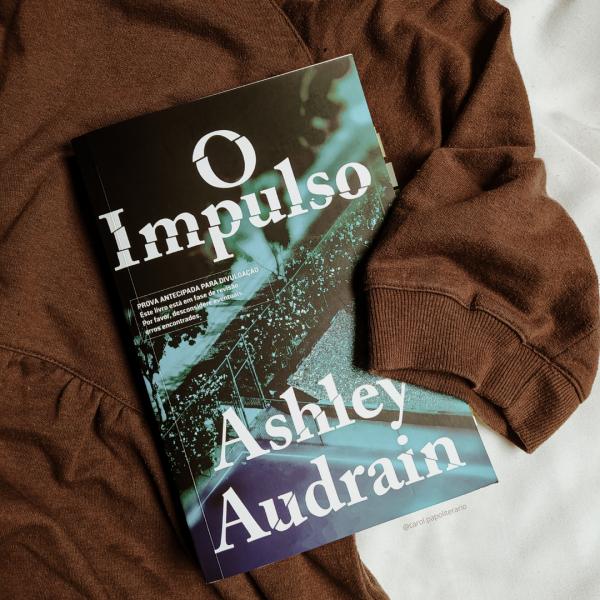 Livro O Impulso, envolto por uma blusa de manga curta, como se estivesse sendo abraçado.