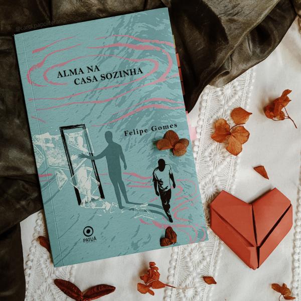 Livro Alma na Casa Sozinha, com um coração de origami do lado direito da imagem, mais abaixo, e folhas secas espalhadas em torno do livro, da metade da imagem para baixo.