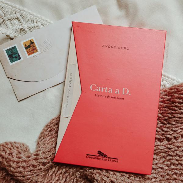 Livro Carta a D em evidência, dentro do box que imita um envelope. Há um envelope de carta com desenhos de selo aparecendo por baixo do livro.