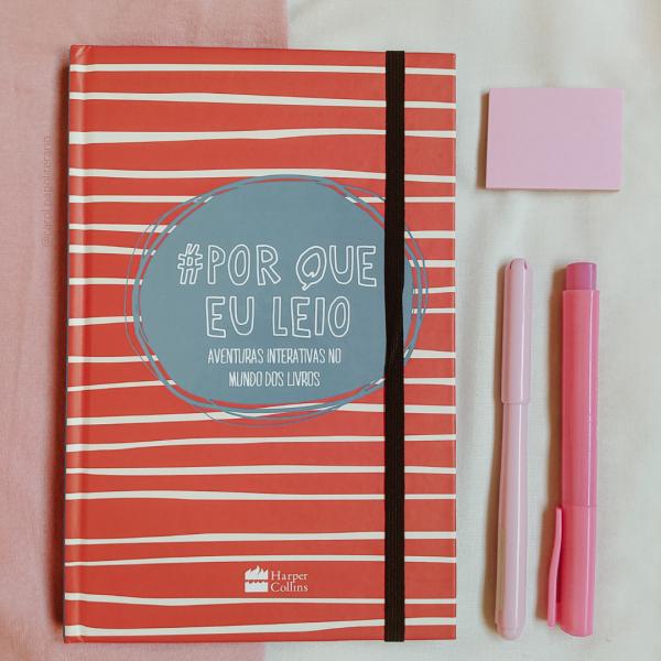 Livro Por que eu leio, com duas canetas rosas e um bloquinho de post-it ao lado.
