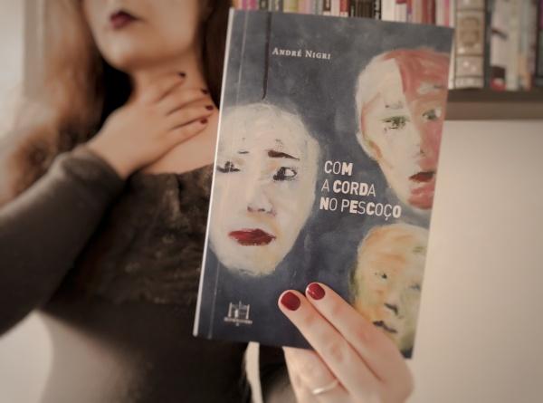 """Livro """"Com a corda no pescoço""""em primeiro plano, segurado por mim, qu estou em segundo plano, com uma das mãos segurando meu pescoço"""