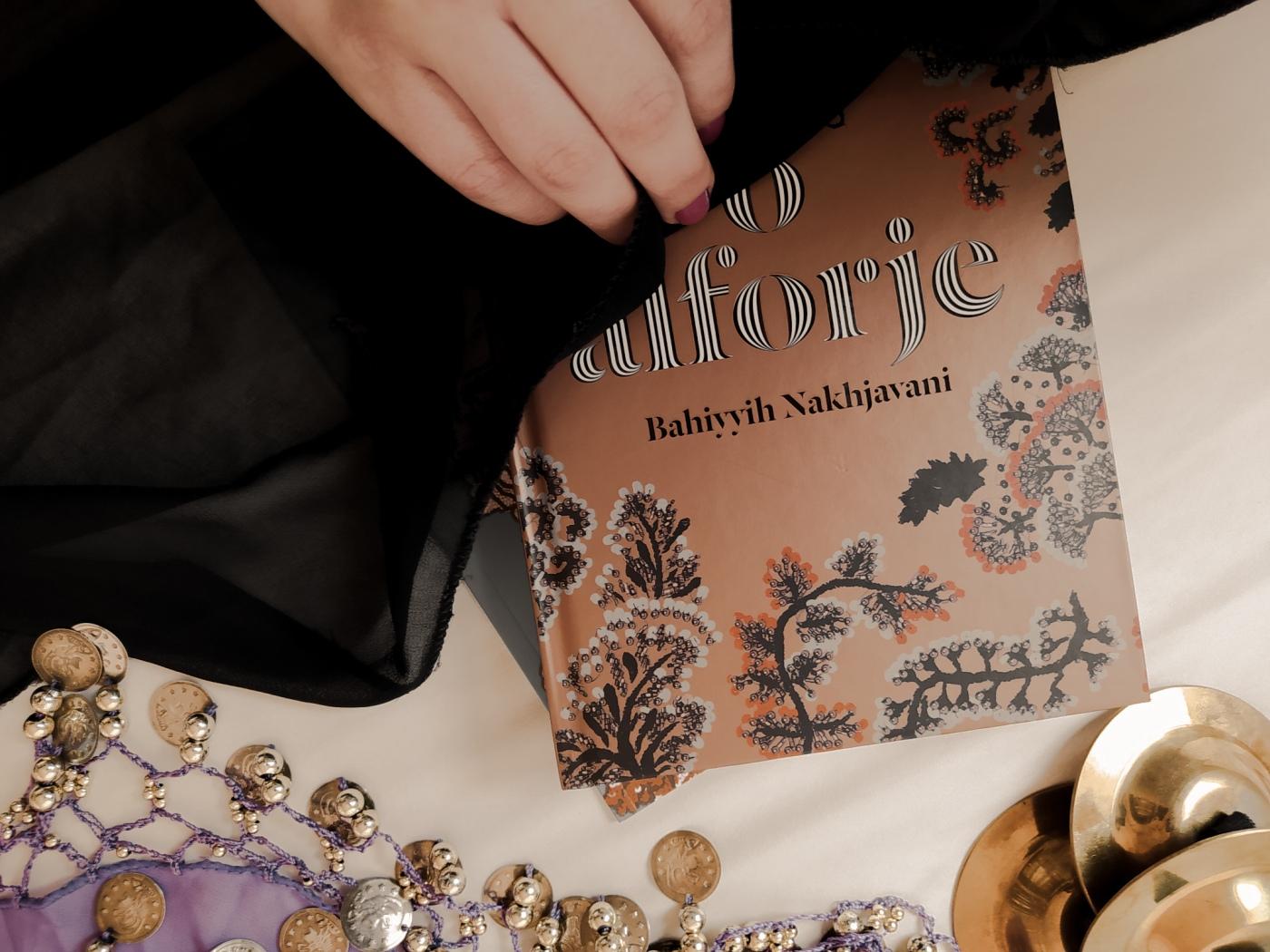 """Minha mão tirando um véu de cima do livro """"O Alforje"""". Abaixo do livro, há um lenço com moedas presas por bordados e três snujs (pratinhos de metal usados na dança do ventre de forma similar às castanholas)."""
